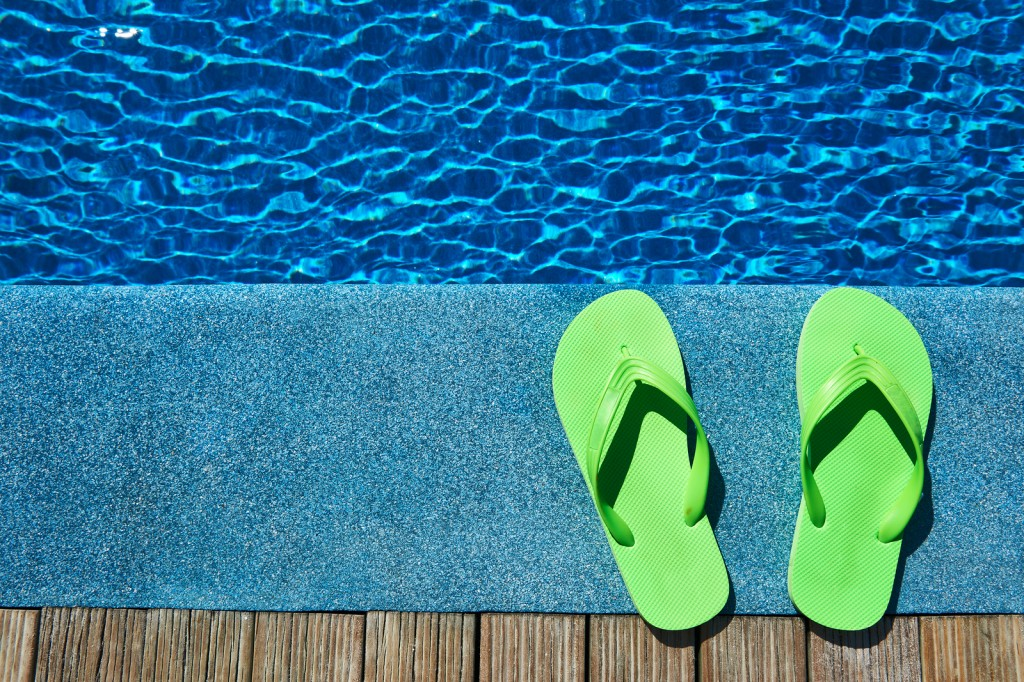 Green slippers by a swimming pool